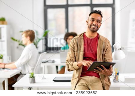 business, technology and people concept - happy smiling indian man with tablet pc computer at office