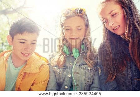 technology, internet and people concept - three happy teenage friends with headphones outdoors looking down at something
