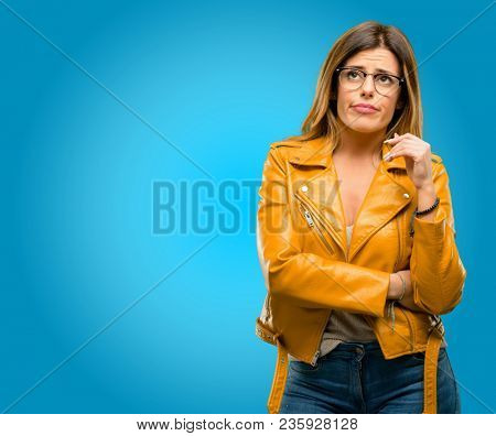 Beautiful young woman with sleepy expression, being overworked and tired, blue background