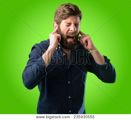Young hipster man with big beard covering ears ignoring annoying loud noise, plugs ears to avoid hearing sound. Noisy music is a problem. over green background