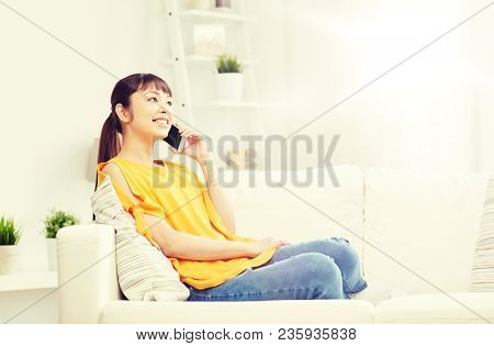people, technology, communication and leisure concept - happy young asian woman calling on smartphone at home