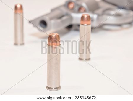 Three .357 Magnum Bullets With A Stainless Loaded Revolver In The Background