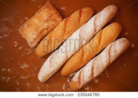 Assortment Of Baked Bread On Wooden Background. Top View.
