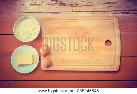 Kitchen Ingredients And Cutting Board On Rustic Wooden Background. Top View With Copy Space.