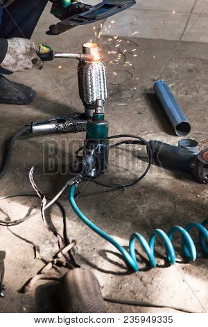 Repairing Of Corrugation Muffler Of Exhaust System In Car Workshop - Mechanic Fixes The Pipe On Corr