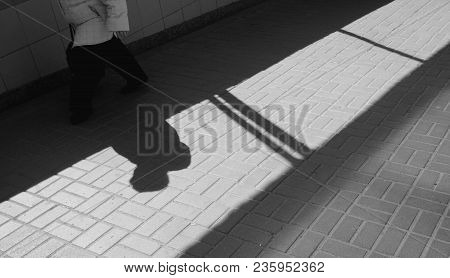 Silhouette Person, Woman Walking  In Underground Passage. Shadow And Light On Paving Slab. Exit From