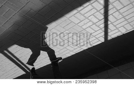 Silhouette Person, Man In Underground Passage. People Silhouette. Shadow And Light On Paving Slab. E