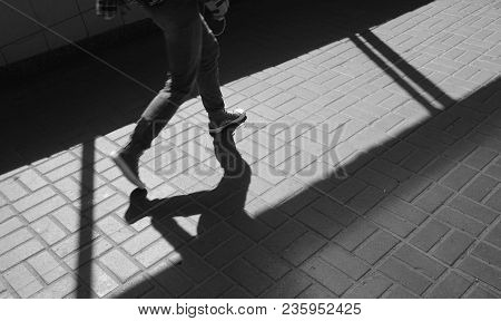 Silhouette Person, Man Walking In Sneakers In Underground Passage. Shadow And Light On Paving Slab.