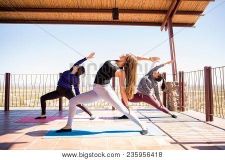 Three Hispanic Women Standing And Stretching Backward In Reverse Warrior Pose At Yoga Class