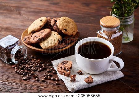 Breakfast Background With Porcelain Mug Of Fresh Black Coffee, Homemade Oatmeal Cookies On Cutting B