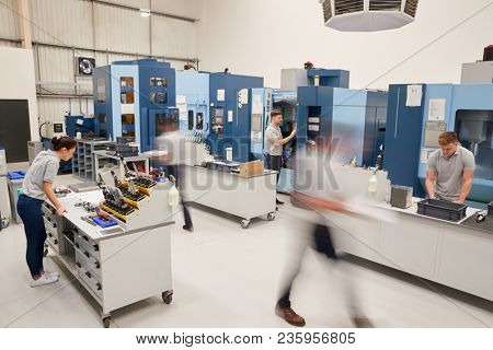 Busy Engineering Workshop With Workers Using CNC Machinery