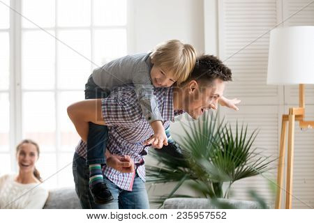 Happy Dad Holding Little Cute Kid Boy On Back Giving Child Piggyback Ride Having Fun Together At Hom