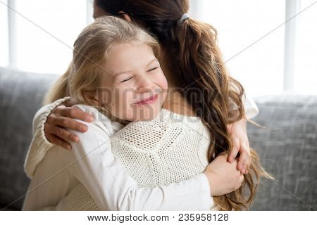 Cute little daughter hugging mother holding tight, mum and happy preschool or school girl cuddling, smiling sincere child embracing mommy, warm relationships and sweet pure kids love for mom concept poster