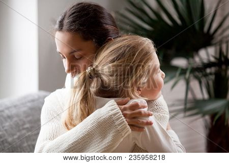 Loving Mother Hugging Cute Little Girl, Young Woman Embracing Adopted Child Holding Tight, Sincere W