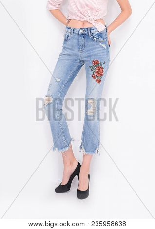 Front view Fashion. Woman legs in embroidered flowers, jeans and black high heels shoes posing