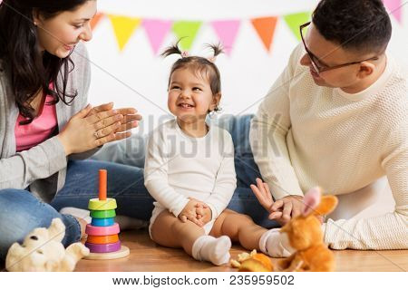 family, holidays and people concept - happy mother, father and little daughter clapping hands on birthday party