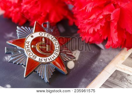 Soviet Order Of Patriotic War (inscription Patriotic War) With Red Carnations Against The Background
