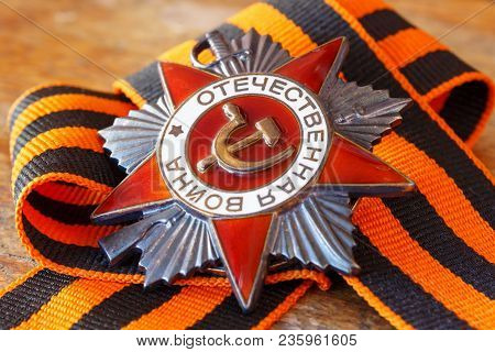 Soviet Order Of Patriotic War (inscription Patriotic War) With St. George's Ribbon On An Old Wooden