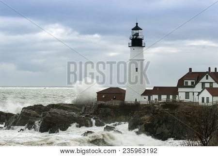 Huge Waves Crash Against Portland Head Lighthouse As Sunlight Breaks Through Storm Clouds. It Is The