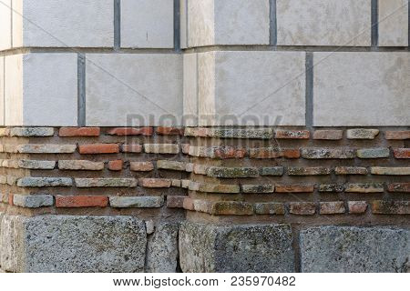 Weathered Brick Wall Made Of Blocks With Various Color And Size, Large White Blocks On Top, Small Re