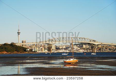 Auckland Harbor bridge, low tide, with city background, New Zealand