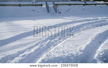 Curved Tire Tracks In The Snow On The Road