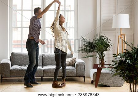 Happy Romantic Couple Having Fun In New Home, Man Holding Womans Hand Up Leading In Dance Enjoying W
