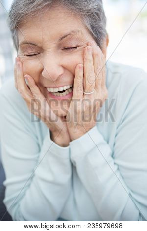Happy Mature Woman With Grey Hair Smiling.
