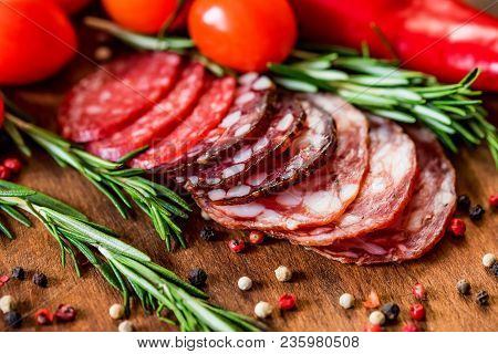 Close Up Image Of Three Sorts Of Cured Sausage On Wooden Board With Fresh Tomatoes, Herbs And Pepper