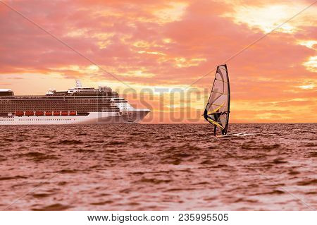 Windsurfer In The Sea With A Cruise Ship On Backgroung. Warm Toned, Lens Sun Flare, Bright Sunset Sk