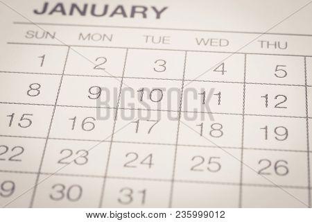 Closeup Dates Of January, Weekly Start On Sunday. Selective Focus On Calendar Shown Dot Prints, Blur