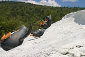Three cute penguin statues sliding down a hill of fake snow. poster