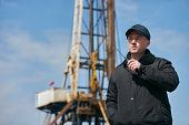 Security guard using portable wireless transceiver. Security man with walkie talkie, standing outdors against oil drilling station platform, safety concept poster