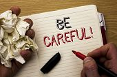 Handwriting text Be Careful. Concept meaning Caution Warning Attention Notice Care Beware Safety Security written by Man Notebook Book Holding Marker the wooden background Pen next to it. poster