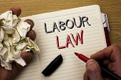 Handwriting text Labour Law. Concept meaning Employment Rules Worker Rights Obligations Legislation Union written by Man Notebook Book Holding Marker the wooden background Pen next to it. poster