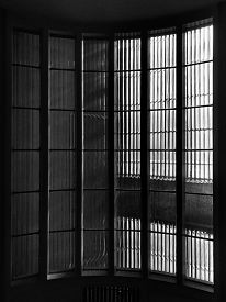 High-contrast Monochrome Image Of Tall, Vertically-curved Department Store Staircase Windows Seen Fr