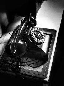 High-contrast monochrome image of black retro-style telephone.