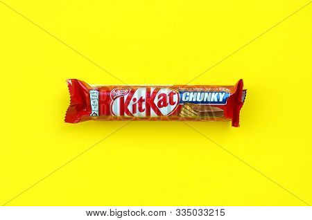 Kit Kat Chocolate Bar In Red Wrapping Lies On Bright Yellow Background. Kit Kat Created By Rowntrees