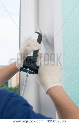 Master In Protective Gloves, Fills The Gap With Silicone To Seal The Installation Of A Plastic Windo