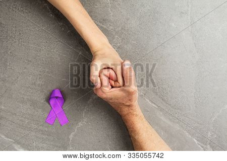 Hands Holding Purple Ribbons Top View On Gray Wooden Background. Alzheimers Disease, Epilepsy, Fibro