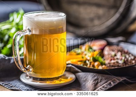 Glass Of Light Beer In Pub Or Restavurant On Table With Delicoius Food.