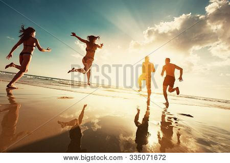 Four Happy Tourists Runs To Sunset Sea Beach. Beach Vacations Concept