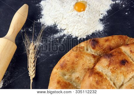 Two Pita Breads With A Golden Crust Lie On A Table Next To Flour, An Egg And A Rolling Pin