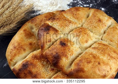 Two Pita Breads With A Golden Crust And Sesame Seeds Lie On A Table With Flour