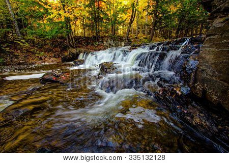 Autumn Michigan Waterfall. Beautiful Slate River Falls Surrounded By Autumn Foliage In Baraga Michig