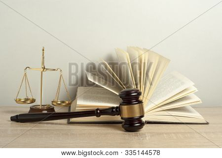 Law Concept. Wooden Judge Gavel , Scales Of Justice And Open Law Book On Table In A Courtroom Or Enf