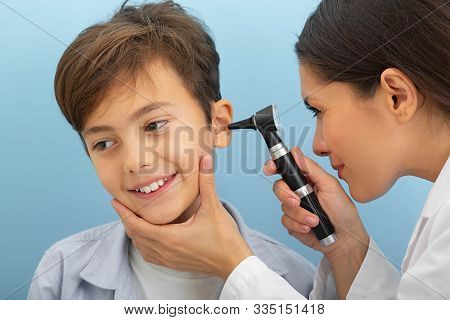 Little Boy While Ear Exam. Ent Doctor Exam Ear With Otoscope On Blue Background