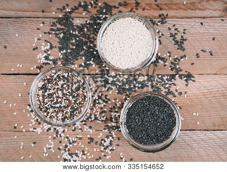 Different Types Of Sesame Seeds. White, Black And Multi-colored Sesame Seeds. Seasonings On A Wooden