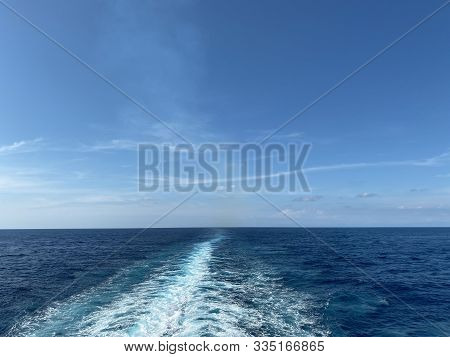 Cruise Ship Wake On A Beautiful Sunny Day With White Clouds And Blue Seas On The Atlantic Ocean.