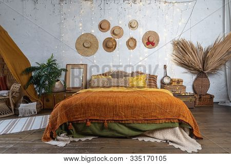 Beautiful Cozy Bedroom With Boho Style Interior, Pillows, Cushions, Green Plants In Flower Pot, Bed